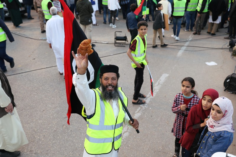 A Libyan protester holds a croissant (La Brioche) as he attends a demonstration to demand an end to the Khalifa Haftar's offensive against Tripoli, in Martyrs Square in central Tripoli