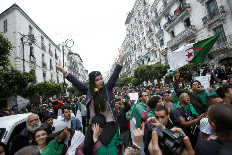 Demonstrators hold flags and banners during peaceful anti-government protests in Algiers
