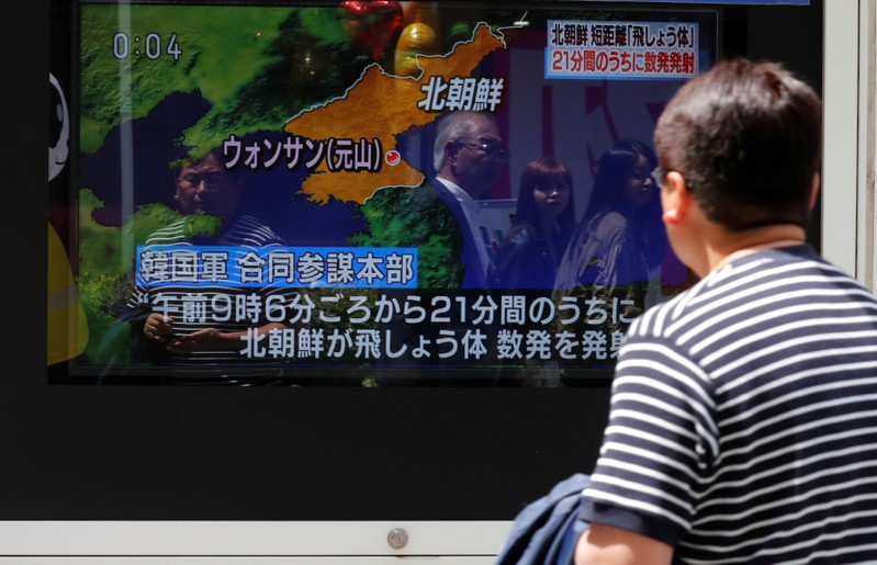 A man watches a television screen showing a news report on North Korea firing several short-range projectiles from its east coast, in Tokyo