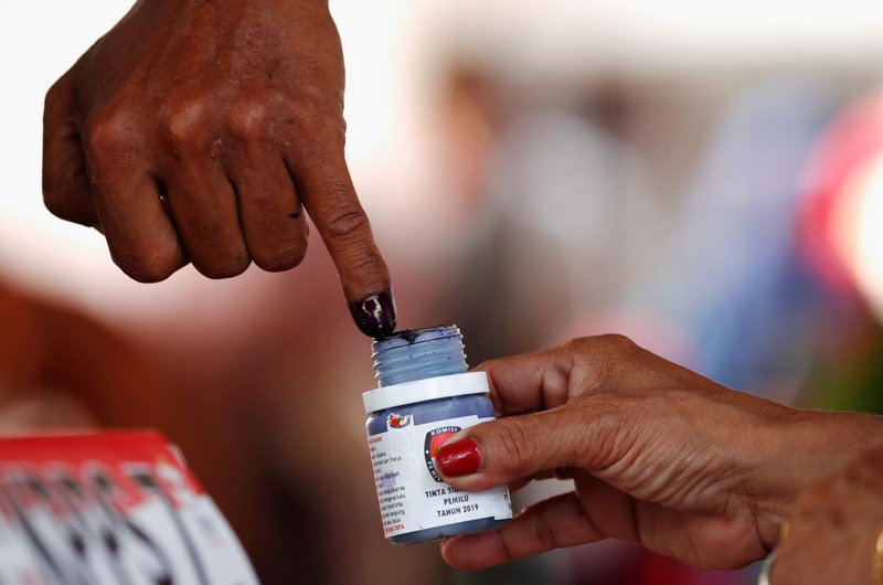 FILE PHOTO: A voter's finger is dipped with ink after voting during elections in Jakarta, Indonesia