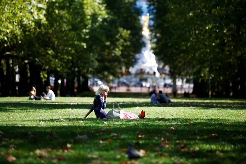 FILE PHOTO: A woman talks on her mobile phone whilst sitting in a park in central London