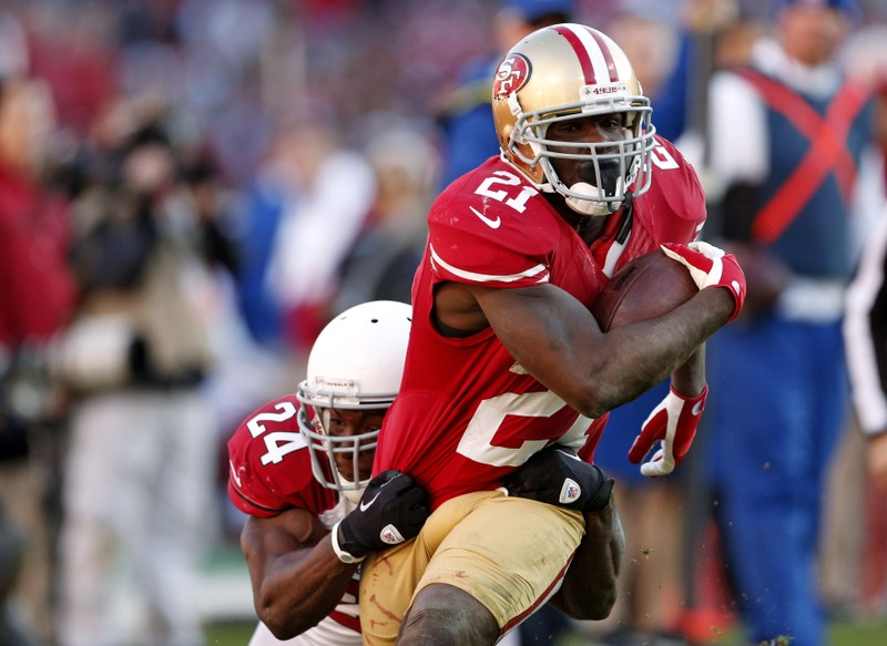 FILE PHOTO: San Francisco 49ers' Gore rushes with the ball as Arizona Cardinals' Wilson tries to tackle during their NFL football game in San Francisco