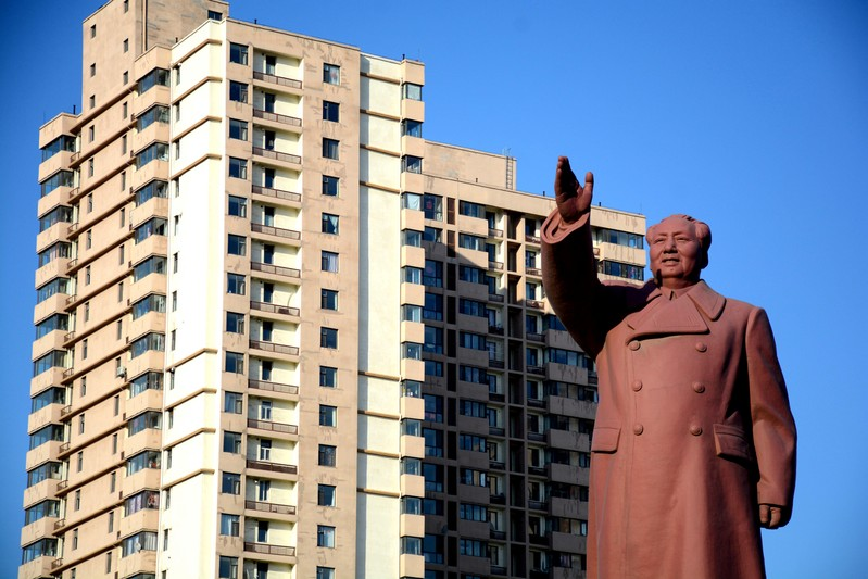 FILE PHOTO: Statue of former Chinese chairman Mao Zedong is seen in front of a residential building in Dandong New Zone