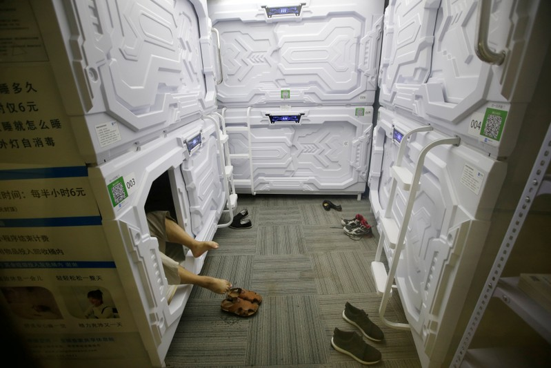 FILE PHOTO: An IT employee takes off shoes as he prepares to sleep in a capsule bed unit at Xiangshui Space in Beijing