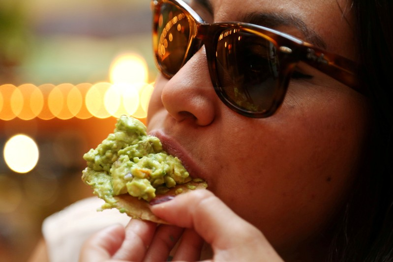 FILE PHOTO: A woman eats guacamole in this picture illustration, in Mexico City