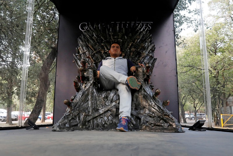 FILE PHOTO: A visitor poses for a photograph as he sits on a replica of the iron throne, as part of the promotion of the final season of