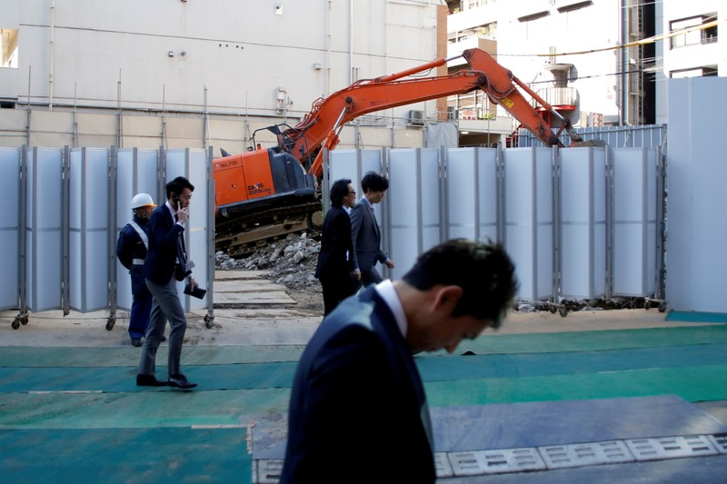 FILE PHOTO: Businessmen walk past heavy machinery at a construction site in Tokyo's business district