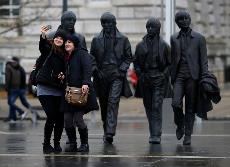 FILE PHOTO: Tourists pose for a selfie in front of a statue of The Beatles  in Liverpool northern England