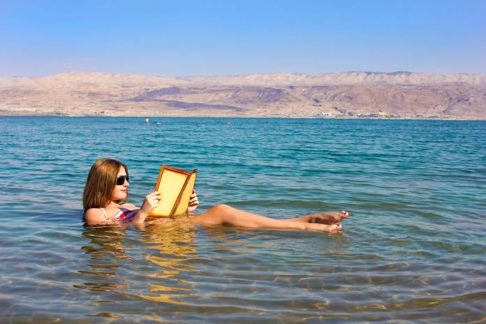 Woman reading while floating in the dead sea