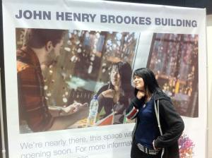Ruthy in college next to an ad