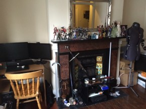Picture of a lounge room in a flat with a collection of figures and swords on the mantle.