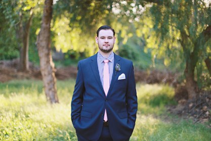 The groom in a navy suit, gingham shirt and blush tie