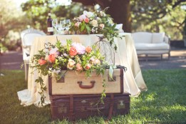 Stack up old suitcases topped with florals to complement a rustic, vintage feel. Photo: Kate Harrison Photography