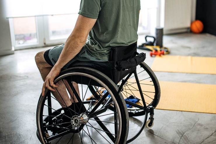 man in wheelchair next to workout gear