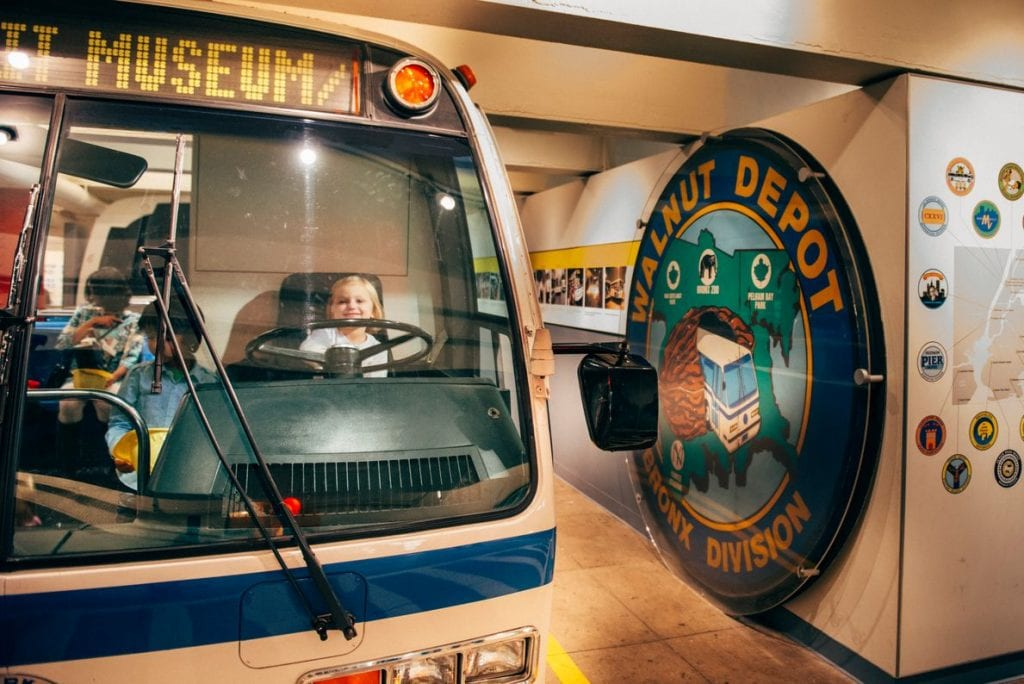 2 children on the bus and 1 child on the bus driver's seat in the New York Transit Museum