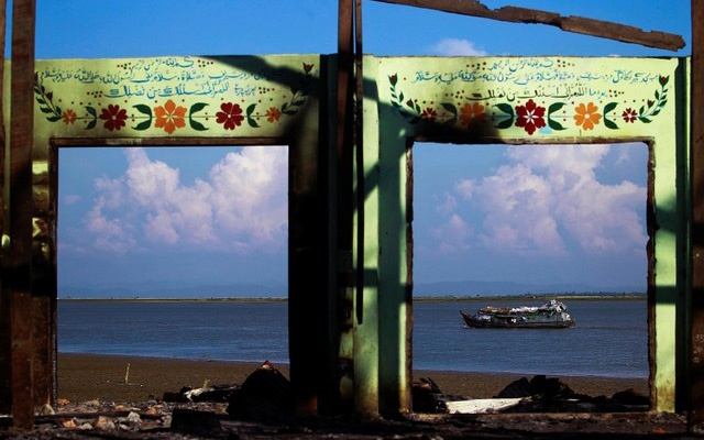 FILE PHOTO: A boat is framed by the ruins of a destroyed mosque in a part of Pauktaw township that was burned in recent violence October 27, 2012. Reuters