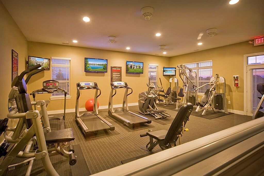 Large cardio and weight machine home gym with televisions on the wall.