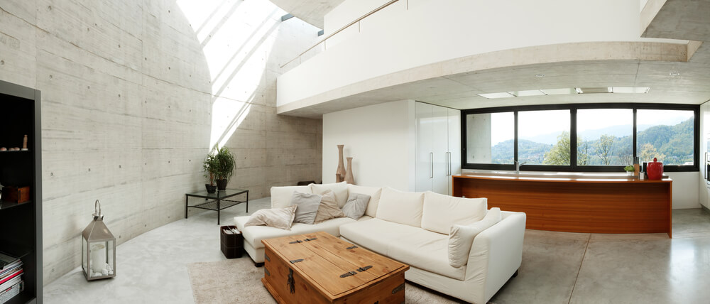 Concrete home with loft room above the kitchen overlooking the living room.
