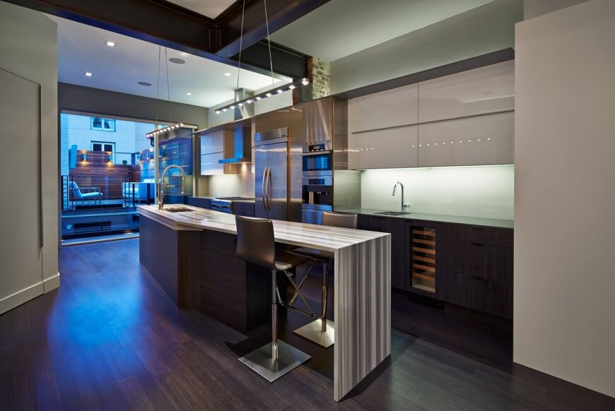 This lengthy, open design kitchen holds a multitude of tones and textures: striped countertop island features dark wood body, matching lower cupboards and flooring, while light glossy upper cabinetry pairs with steel appliances beneath dark exposed metal beam ceiling. Space extends onto rooftop patio in rear.