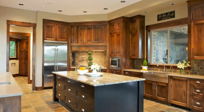 Wide kitchen design features dark natural wood cabinetry throughout, surrounding a massive black island with light marble countertop over earth tone tile flooring.