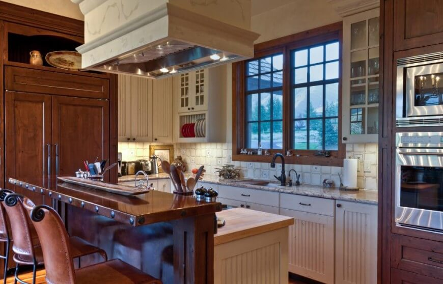 Here we see the prior kitchen from a wider view, with elaborate painted hood vent standing over two-tier island with dark wood dining space at left. White tile backsplash adds detail beneath glass door upper cupboards.