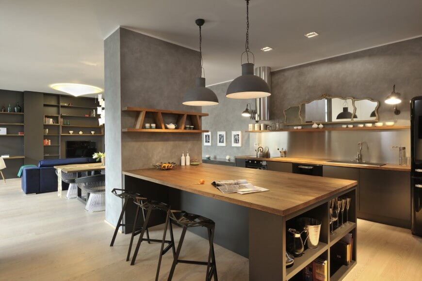 Large open space shares living, dining, and kitchen areas, with single grey dividing wall at center. Natural wood topped island in black features ample dining space and shelving, while kitchen counters match the tone, with brushed aluminum backsplash and built-in wall shelving.