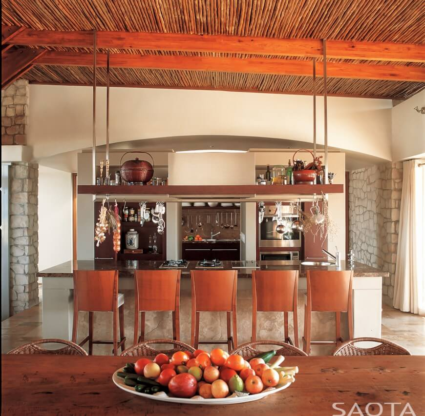 Rustic yet modern look kitchen pairs warm natural wood toned table and seating with beige stone walls, island, and brown marble countertop. Natural wood pot rack and built-in shelving around appliances stand out beneath wood ceiling with exposed beams.