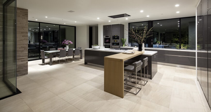 Here's another minimalist, modern open space kitchen design. The two-segment island comprises a glossy grey body with white marble countertop, with attached natural wood dining space extension. Beige marble flooring throughout expends toward full-height exterior glass walls all around.