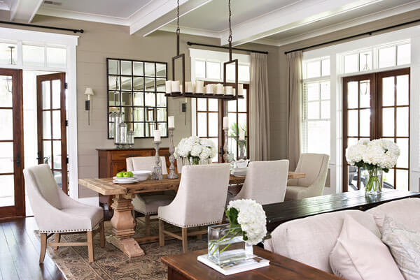 Rustic dining table with plush chairs. Wooden side tables separate dining room from living room. Three sets of glass doors lead outside. Various hydrangea arrangements tie the rooms together.