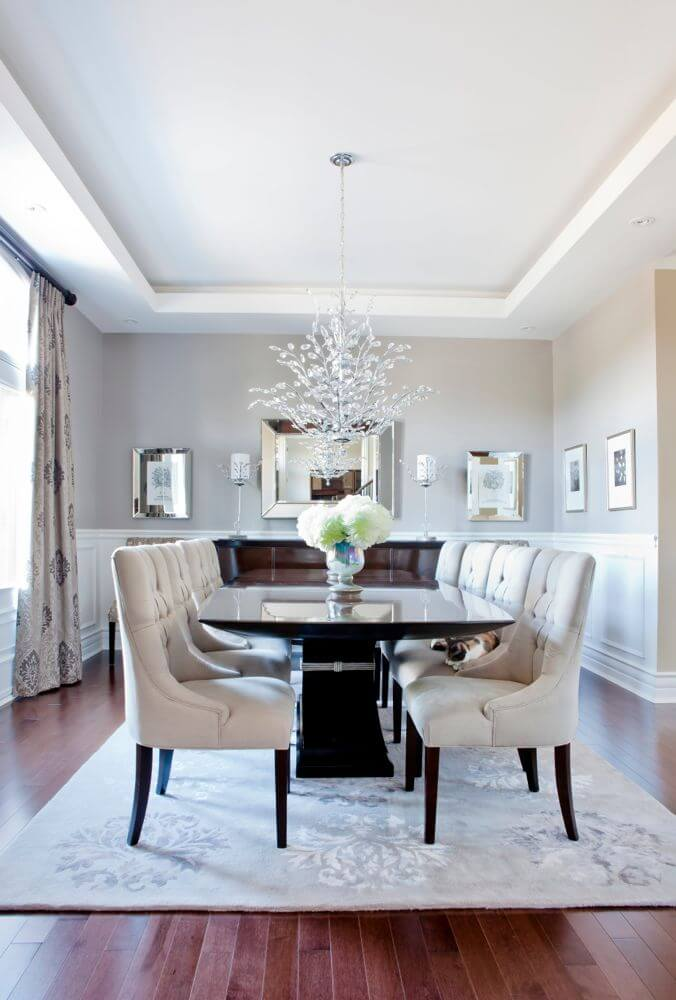Glossy contemporary dining table matched with plush dining chairs. Patterned curtains match the cream rug covering the hardwood floor. Large glass chandelier acts as a focal point.