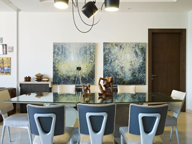 An open dining room with view of a seating area. Glass-topped table reflects artwork on back wall. Matching wooden sculptures serve as a centerpiece for the table.