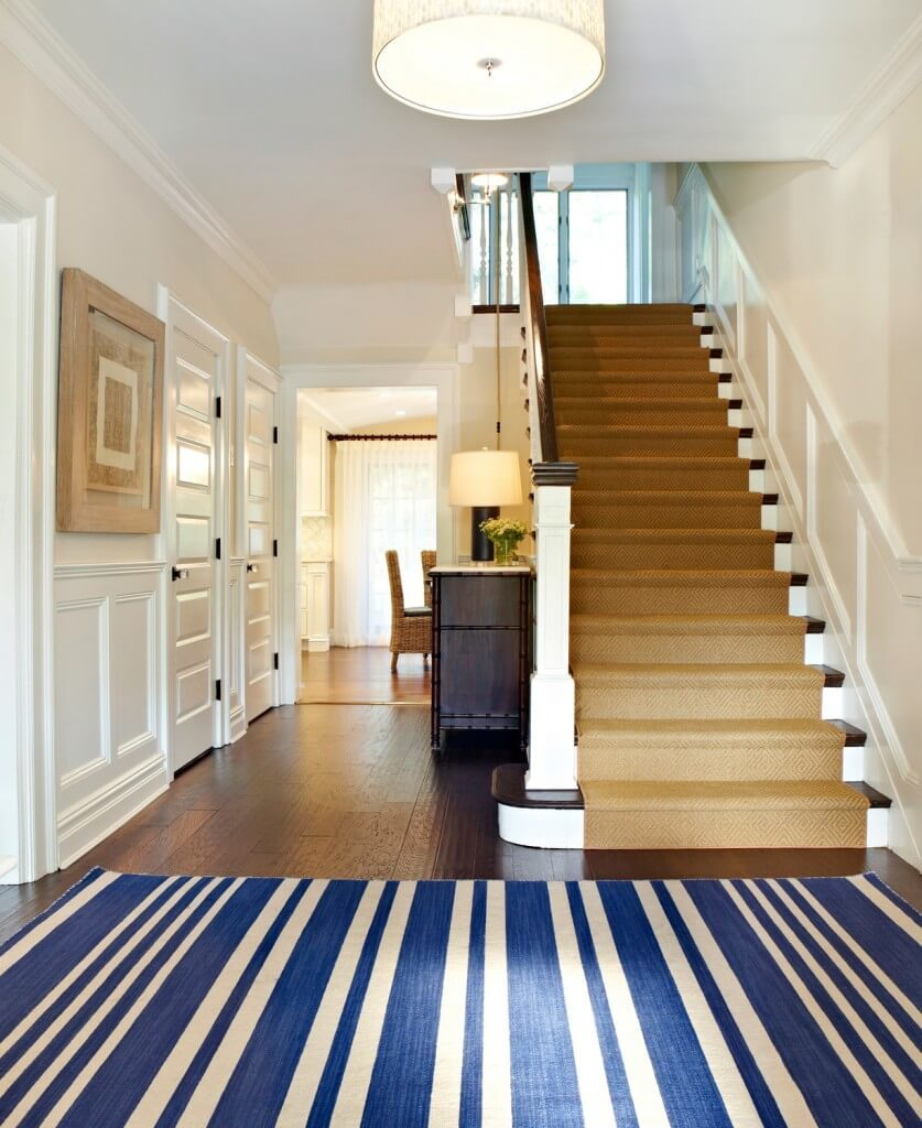 Dark floors are brightened with white walls and warm, camel colors used through the room. A boldly striped, bright navy rug brings a pop of color in to the space while accenting the colors already present in the room. Dark wood accents found in the banister, stairs, and wardrobe bring extra depth to the room.