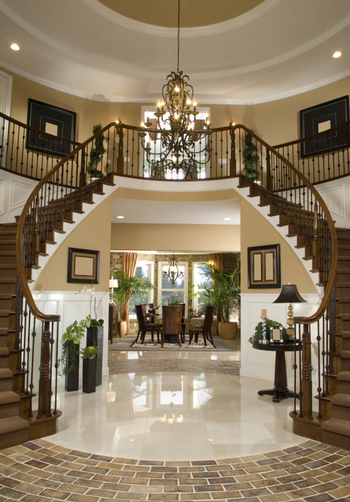 A stately staircase like this one demands to have a color scheme that matches. Surrounding the marble floor in a stunning brick circle allows the shape of the stairs to influence the rest of the room. Dark accents balance the lighter colors used to brighten the space up and highlight the stairs even more.