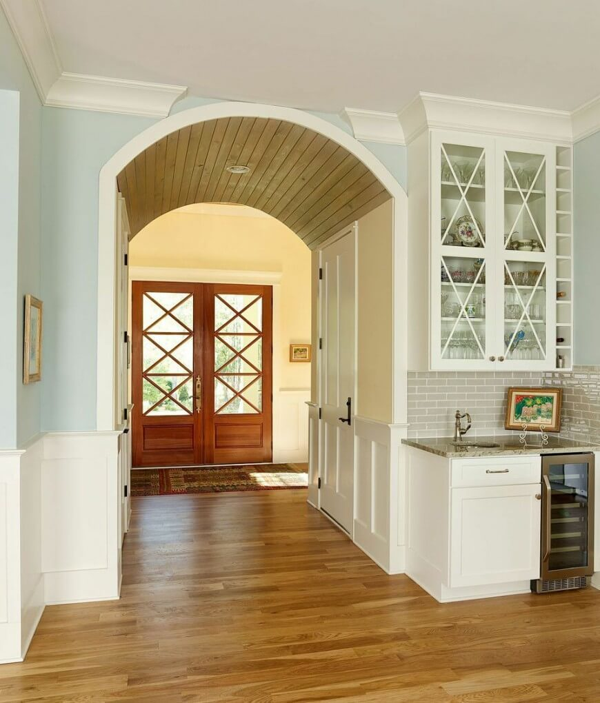 The wooden slats that make of the ceiling of the arch brings a unique touch to this room, framing the double front door nicely. The use of pale yellow walls giving way to a bright and calming blue in the kitchen creates a charming color combination while the rich colors of the rug in front of the door brings more to the space.