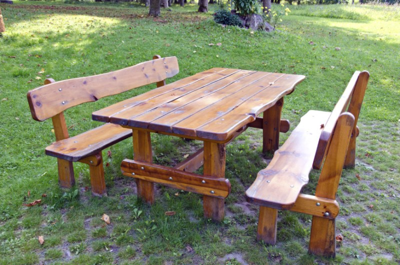 Here is a picnic table with separate benches. The wood is finished but has a natural shape. This naturalistic wood gives this picnic table a rustic and outdoorsy look. This aesthetic is amazing if you want your backyard to take you back to nature.