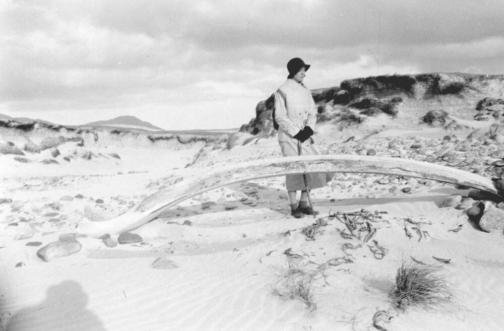 A black and white photograph of a woman standing on a sandy beach with dunes, just behind a very large jaw bone, probably from a whale. The shadow of a person wearing a hat is cast upon the sand in the bottom left corner.