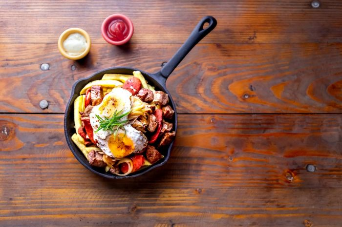 french fries topped with sliced beef, tipical sausages chorrisos, fried onion and eggs served in iron cast pan with sauces