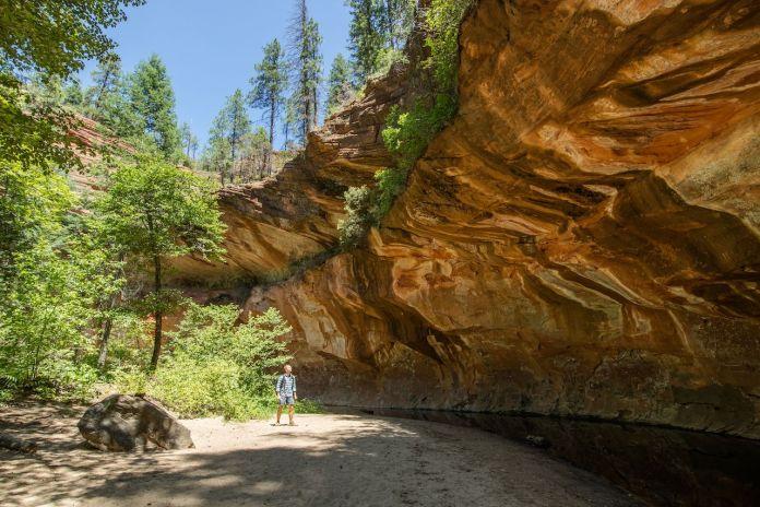 Man trekking through Oak Creek Canyon on the West Fork trail in Arizona