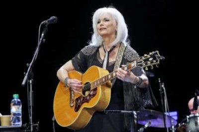 Emmylou Harris playing the guitar on stage