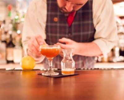bartender adding a garnish to a cocktail