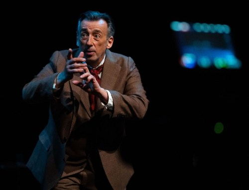 man in brown suit performing