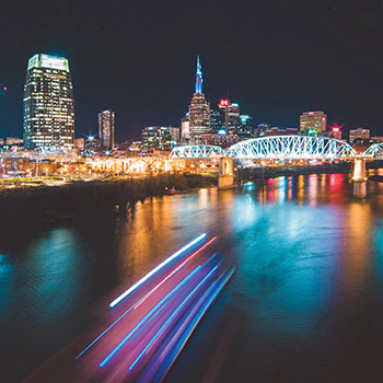 Nashville skyline at night with lights reflecting in the water