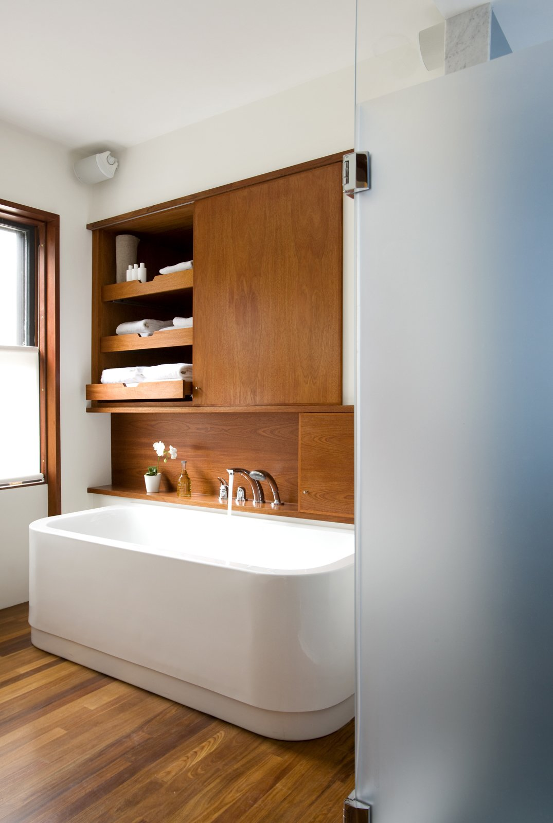 "The leftmost cabinet above the Duravit bathtub (equipped with KWC fixtures) occupies the space where a doorway once lead into the living room, creating unnecessary traffic from the home's public spaces through to the master bedroom. The new bathroom features a minimal palette of white and teak. ""It's able to hold up on boat decks so is good for a bathroom,"" Klug says. It also makes the heated floor that much nicer to walk on in the morning."
