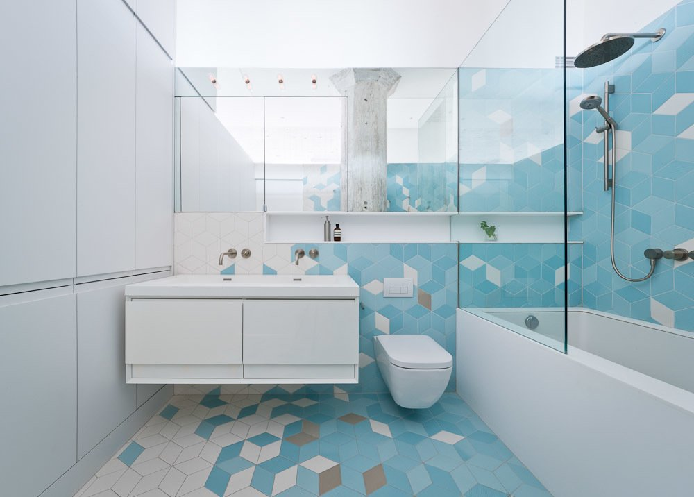 The bathroom, located just adjacent to the kitchen, features a pattern of gray and turquoise tiles that climbs from the floors up the walls. They serve as a burst of color among the predominately white walls elsewhere, transforming the bathroom into one of the apartment's most striking spaces.
