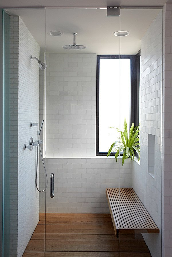 A clean and simple shower in Chicago is lined with modern subway tiles and a wood shower bench.