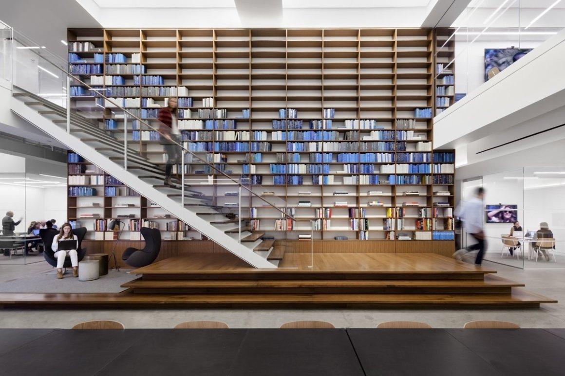 Ce mur de livres soigneusement arrangés dans les bureaux de Warby Parker à New York met l'accent sur leur couleur de marque principale d'une manière unique.