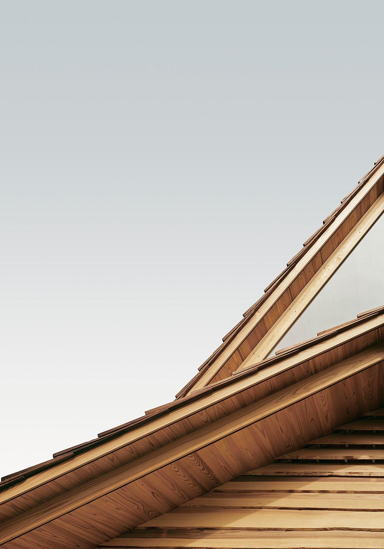 Les avant-toits extérieurs empilés placés dans un cèdre chaud contrastent avec les rayons neutres et neutres du ciel de Yoshino.