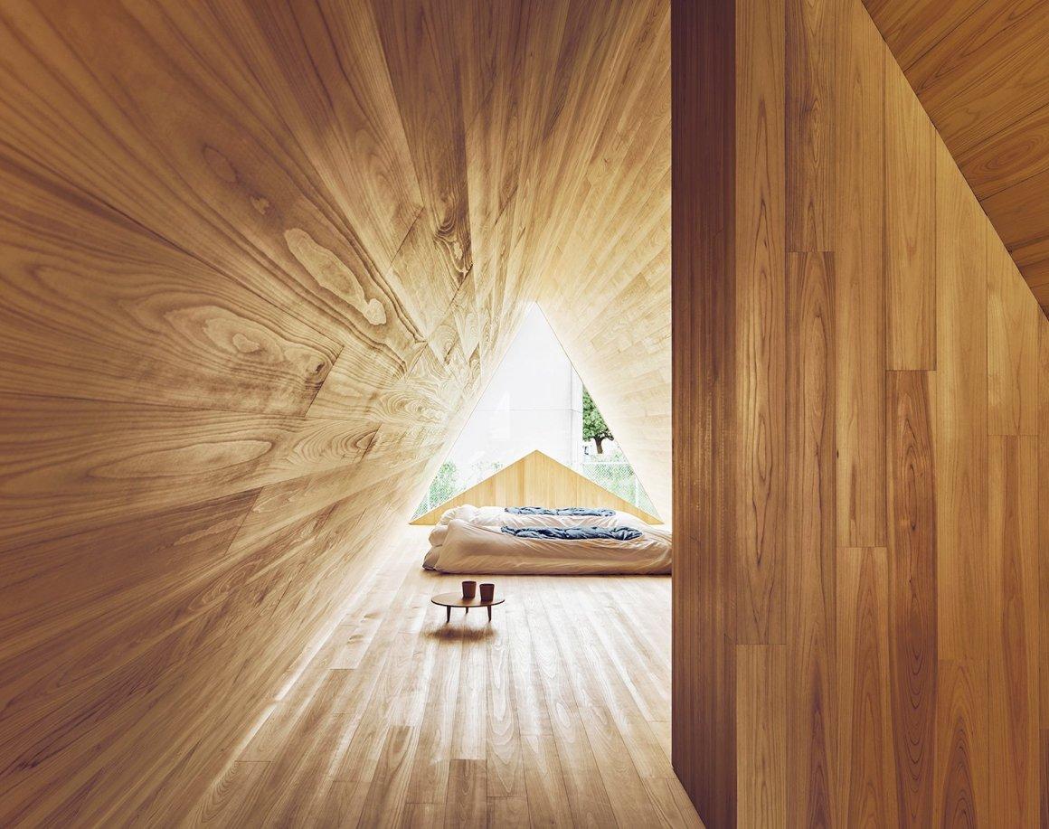 """L'espace de la chambre est rétro-éclairé par une forme unique """"A"""" qui offre une grande lumière naturelle qui reflète les tons chauds et structurés du cèdre."""