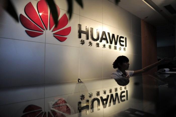 2012年に中国中央部の湖北省武漢にあるHuaweiオフィスのカウンターの後ろに受付係が座っています。撮影:STR / AFP / GettyImages
