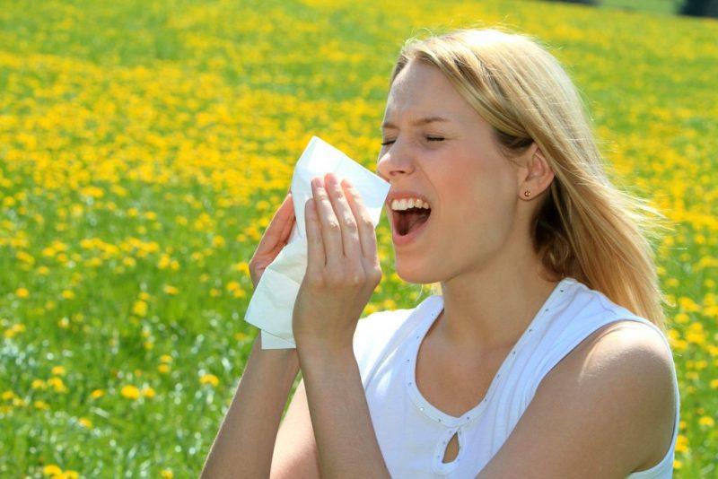 Mujer estornudando al estar en contacto con la luz solar